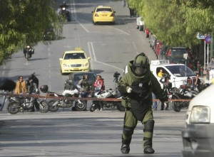 A police explosives expert arrives to detonate a suspicious package in Athens